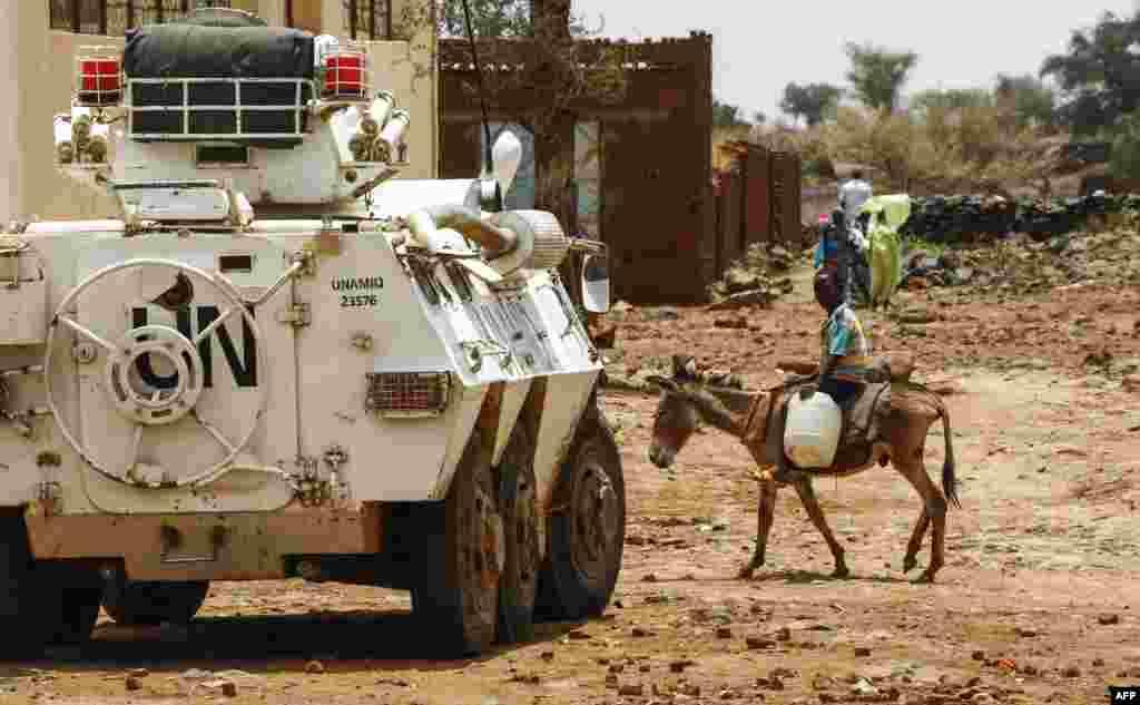 Seorang remaja Sudan menaiki keledai melewati kendaraan militer pasukan penjaga perdamaian PBB (UNAMID) di Golo, Darfur tengah.