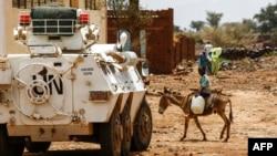 Seorang anak laki-laki Sudan mengendarai keledai melewati kendaraan lapis baja PBB-Uni Afrika di Darfur (UNAMID) di kota Golo yang dilanda perang, di daerah pegunungan berhutan lebat Jebel Marra, Darfur tengah, 19 Juni 2017. (Foto: dok).