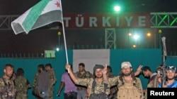 지난 6월 터키와 접경 지역 시리아 검문소를 점령한 쿠르드족 민병대가 깃발을 흔들고 있다. (자료사진)