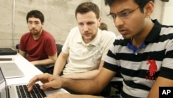 Shiva Gopalan, an international and computer engineering master's student at Texas A&M University (far right), confers with IBM developers Henrique Copelli Zambon (center) and Luiz Aoqui, during an IBM hosted Spark Hackathon at Galvanize, a tech hub in San Francisco on Sunday, June 14, 2015. (George Nikitin/Feature Photo Service for IBM)