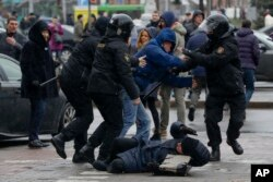 FILE - A woman, pushed to the ground by Belarus police, tries to defend herself during an opposition rally in Minsk, March 25, 2017.