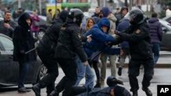 在明斯克的反對派集會中,一名被白俄羅斯警察撲倒在地的婦女試圖自我保護(2017年3月25日)