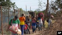 "FILE - Venezuelans illegally cross into Colombia, to Villa del Rosario, along a path known as a ""trocha,"" Aug. 31, 2018."