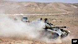 Tentara pemerintah Suriah dengan tanknya mengambil posisi dekat gerbang masuk kota Palmyra, Suriah tengah (24/3).
