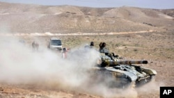 Soldats syriens prenant position à l'entrée de Palmyre, le 24 mars 2016 (SANA via AP)