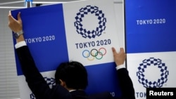 A staff takes out a banner featuring Tokyo 2020 Olympics emblem from the wall after a news conference hosted by International Olympic Committee (IOC) Vice President John Coates and President of Tokyo 2020 Olympic and Paralympic organising committee Yoshir