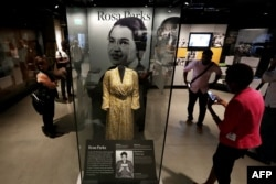 FILE - Civil Rights pioneer Rosa Parks' dress is on display in the concourse galleries at the Smithsonian's National Museum of African American History and Culture on the National Mall Sept. 14, 2016 in Washington, D.C.