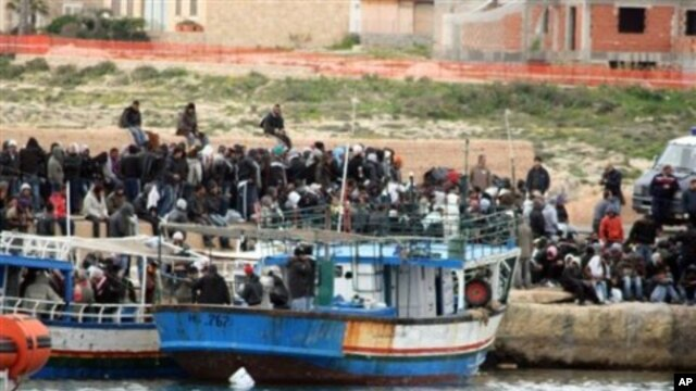 Would-be migrants believed to be from Tunisia are seen on the shores of the Sicilian island of Lampedusa, Italy, after arriving there by boat, February 11, 2011
