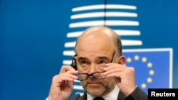 FILE - European Commissioner for economics, taxation and customs Pierre Moscovici attends a press conference after an eurozone finance ministers meeting in Brussels, Dec. 8, 2014.
