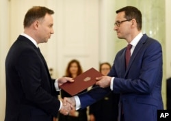 Polish President Andrzej Duda, left, formally designates Finance Minister Mateusz Morawiecki for the prime minister's post, in Warsaw, Poland, Dec. 8, 2017.