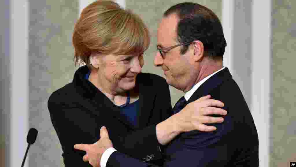 French President Francois Hollande, right, and German Chancellor Angela Merkel hug each other after their marathon talks in Minsk, Belarus, Feb. 12, 2015.