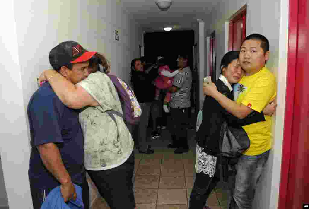 People embrace on the upper floor of an apartment building located a few blocks from the coast where they gathered to avoid a possible tsunami after a powerful magnitude-8.2 earthquake in Iquique, Chile, Apr. 1, 2014.