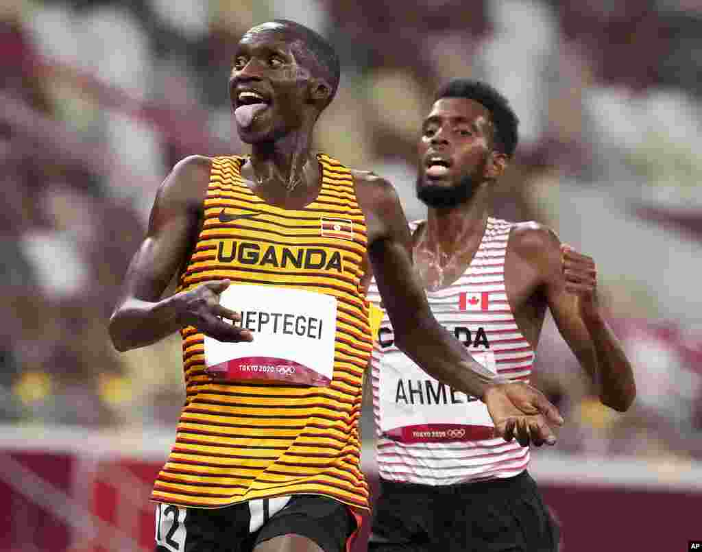 Joshua Cheptegei, of Uganda, leads Mohammed Ahmed, of Canada, silver, to win the gold medal in the final of the men's 5,000-meters at the 2020 Summer Olympics, Friday, Aug. 6, 2021, in Tokyo, Japan. (AP Photo/Charlie Riedel)