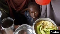 A boy waits for food during a food distribution from an international Non-government Organization (NGO) in Mogadishu June 30, 2012
