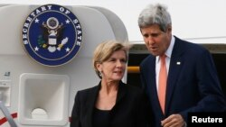 U.S. Secretary of State John Kerry (R) steps off his aircraft alongside Australia's Foreign Minister Julie Bishop in Sydney, August 11, 2014.
