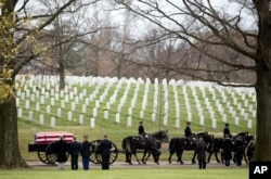 Horse-drawn caisson leads a funeral procession at the Arlington National Cemetery in April 2014.