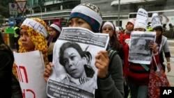 Para pekerja domestik dan pendukung mereka memegang gambar pembantu rumah tangga asal Indonesia, Erwiana Sulistyaningsih yang berusia 23 tahun dan disiksa secara brutal oleh majikannya di Hong Kong. (Foto: Dok)