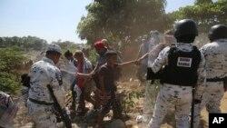 Un joven migrante centroamericano es retenido por sus compañeros, ya que son bloqueados por la Guardia Nacional Mexicana después de cruzar el río Suchiate con un grupo de migrantes de Guatemala a México, en la orilla del río cerca de Ciudad Hidalgo.