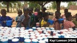 Les élèves de l'école primaire publique de Louanga à l'heure de la distribution de la nourriture, Togo, 23 mai 2017. (VOA/Kayi Lawson).