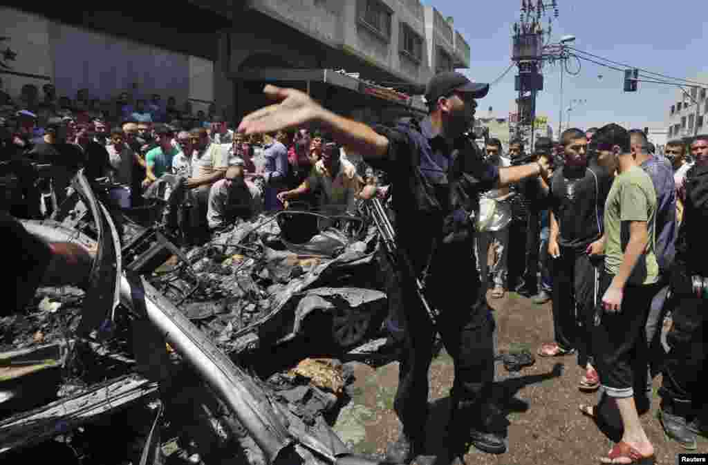 A police officer gestures as Palestinians inspect the remains of a car which police said was targeted in an Israeli air strike in Gaza City, July 8, 2014.