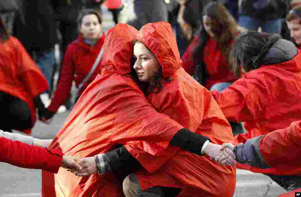 罗马尼亚志愿者在首都布达佩斯手拉手用人体组成一条代表抗击艾滋病的红丝带。(Reuters)