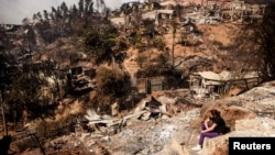 A resident whose home was destroyed by a major fire sits amid the destruction in Valparaiso, Chile, April 13, 2014.