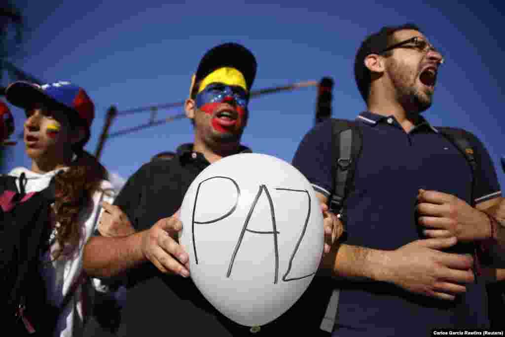 Apoiadores do líder da oposição, Leopoldo Lopez, gritam durante um comício para promover a paz em Caracas, 20 de Fevereiro de 2014. As forças de segurança venezuelanas e manifestantes se enfrentaram nas ruas bloqueadas por barricadas em chamas em várias cidades provinciais na quinta-feira.
