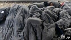 Parte de los fondos se dedicarán para ayudar a mujeres y niñas en el sur Europeo. En la fotografía un grupo de migrantes duerme sobre los rieles de un tren en la frontera norte de Grecia.