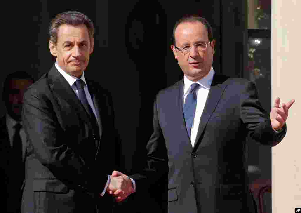 French President-elect Francois Hollande, right, shakes hands with outgoing President Nicolas Sarkozy before the handover ceremony Tuesday, May 15, 2012 at the Elysee Palace in Paris.
