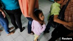 FILE - Women and their children wait in line to register at the Honduran Center for Returned Migrants after being deported from Mexico, in San Pedro Sula, northern Honduras June 20, 2014.