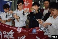學生代表撕爛紙製的「推普機」,反對當局推行普教中。(美國之音湯惠芸攝)