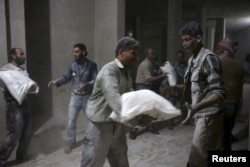 Men store bags of flour unloaded from a Red Crescent aid convoy in the rebel held besieged town of Jesreen, in the eastern Damascus suburb of Ghouta, Syria, March 7, 2016.