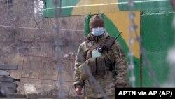 На фото: військовий у масці на пропускному пункті у Майорську, Донецька область
