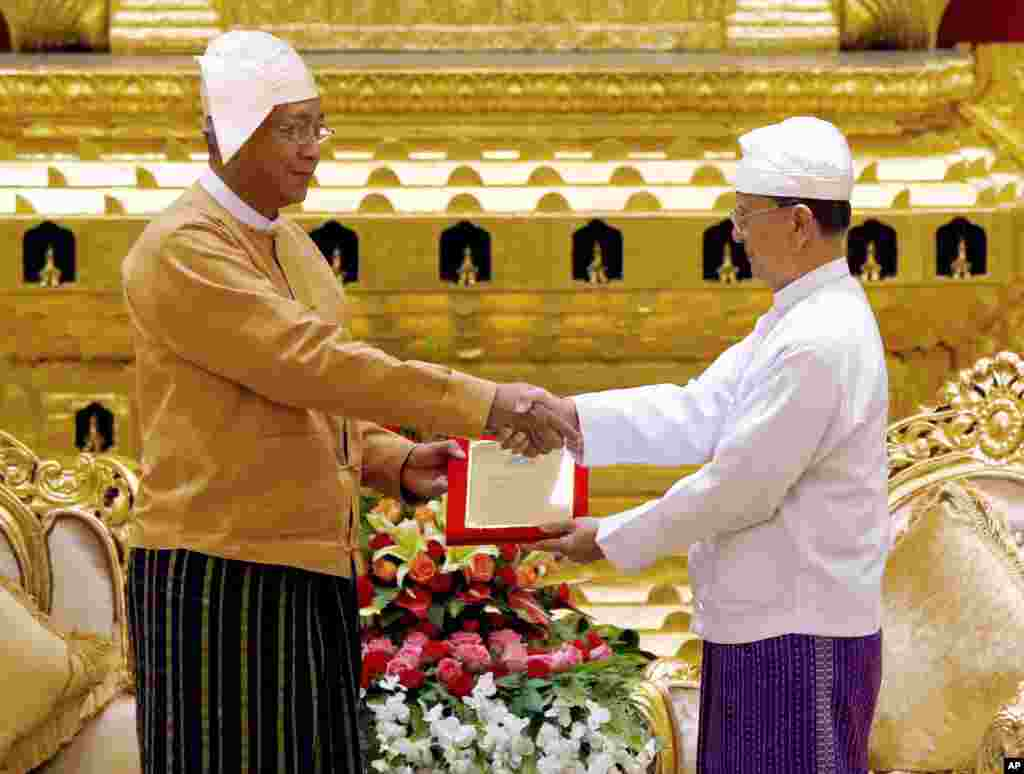 Myanmar's new president Htin Kyaw, left, receives the presidential seal from outgoing president Thein Sein, during a handover ceremony in Naypyitaw, March 30, 2016.