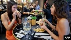 """Thực khách thưởng thức món bánh kẹp làm từ """"thịt gà nuôi nhân tạo"""" tại một nhà hàng ở Ness Ziona ở Israel hôm 18/6. Một công ty của Trung Quốc vừa công bố các món từ thịt lợn nuôi trong phòng thí nghiệm và sẽ cung cấp cho thị trường tiêu thụ lớn nhất thế giới này."""