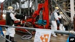 Para pekerja mengebor pipa ke dalam tanah yang digunakan untuk menciptakan dinding bawah tanah beku di PLTN Fukushima, timur laut Tokyo, Juli 2014. (AP/Kimimasa Mayama)