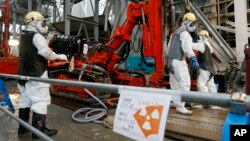 Para pekerja di reaktor nuklir Fukushima, Juli 2014.
