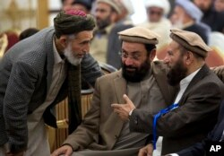 FILE - Afghanistan's former PM Ahmad Shah Ahamdzai, right, talks with an Afghan delegate as Ghairat Baheer, center, head of political cell Hizb-e-Islami Afghanistan listens during a conference title 'Peace and Reconciliation in Afghanistan', in Islamabad.