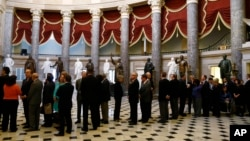 FILE - Members of Congress line up to file onto the House floor for a vote, on Capitol Hill in Washington.