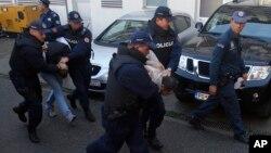 Crnogorska policija privodi osumnjičene na saslušanje u izbornom danu, 16. oktobra 2016. (AP Photo/Darko Vojinovic)