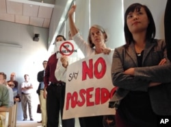 FILE - Scores of supporters and critics of a proposed $900 million desalination plant pack a meeting of the California Coastal Commission, in Huntington Beach, Calif., Nov. 13, 2013. Builder Poseidon Water hopes to begin construction in 2016.