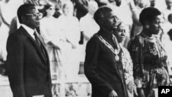 FILE: Zimbabwe's Prime Minister, Robert Mugabe, left, President Canaan Banana, center, his wife Janet, and an unidentified woman, stand during a military parade past Salisbury's Rufaro soccer stadium, April 18, 1982, during celebrations marking Zimbabwe's second anniversary. (AP)