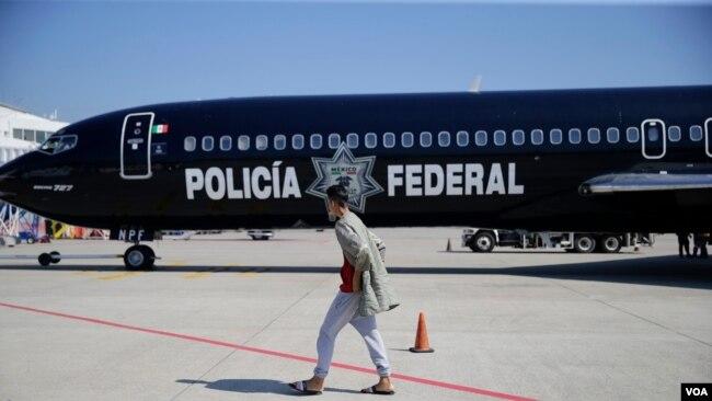 Migrante hondureño camina frente al avión mexicano que lo devolció a su país.