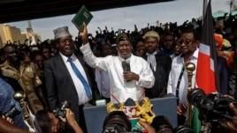 Opposition leader Raila Odinga (C) accompanied by lawyers Miguna Miguna (C-L), Tom