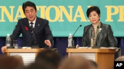 Ruling Liberal Democratic Party leader and Japan's Prime Minister Shinzo Abe, left, speaks as Party of Hope leader Yuriko Koike, listens during the party leaders' debate for the Oct. 22 lower house election in Tokyo, Oct. 8, 2017.