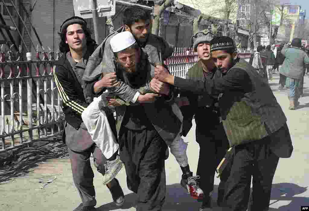 Dân Afghanistan khiêng một người đàn ông bị thương trong cuộc biểu tình chống Mỹ ở tỉnh Kunduz, phía bắc thủ đô Kabul, ngày 25/2/2012
