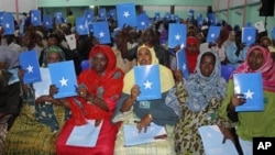 Somalia's constituency assembly members hold up copies of the proposed new constitution during the beginning of a nine-day meeting in Mogadishu, July 25, 2012.