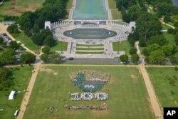 华盛顿国家大草坪上的芳草和绿树,人们用白色绿色和棕色的伞组成图案,庆祝国家公园系统建立100周年(2016年8月25日)