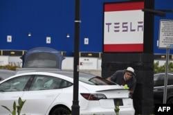 Seorang karyawan Tesla membersihkan sebuah mobil di showroom Tesla di Burbank, California, 24 Maret 2020. (Foto: AFP)