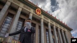 资料照:一名中国保安官员在正在举行全国人大会议的北京人大会堂外警卫。(2020年5月25日)